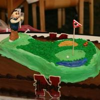 Golf, Bears, And Husker Fan Cake Choc. with Godiva chocolate BC. 11 by 14 with an inverted Dora pan for the golfing green. Figurine is fondant as is the snake (son in law...