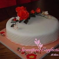 Orange Gumpaste Roses On Fondant Covered Oval Cake for a friend's retirement