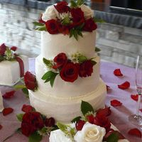 Tiered White Cake With Red Roses this cake is very plain with red and white roses-there are three smaller square cakes with it that are meant to look like gift packages