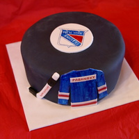 Hockey Puck Cake Hockey puck cake with Ne York Rangers logo. I hand painted the logo. Jersey has the kids last name, and the hockey stick has happy birthday...
