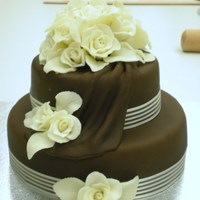 Chocolate Wedding Cake Chocolate mud cake with chocolate fondant covering & draping and white chocolate modeling paste roses. Made in class at Greensborough...
