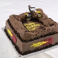 Dirt Bike Cake frosted in chocolate buttercream. Track is made out of rice krispies. With oreo cookie crumbles. the flames are colorflow.