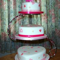 "Hearty Party Three heart shaped tiers 10"" 8"" and 6"" covered in sugarpaste with sugarpaste hearts in two shades of pink and gold to look..."