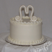 "Simply M Just a quick cake for a friend.....buttercream with a ""M"" made of fondant, fondant flowers"