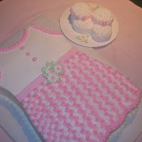 Baby Dress With Booties 11 X 15 Sheet cut into shape of dress. Booties are made from 1 and 1/2 cup cakes. Decorations are buttercream, edible pearls, and royal...
