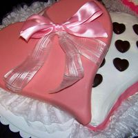 Box Of Chocolates Heart-shaped cake with buttercream icing. Chocolate candies for candy pieces and lid is made from molded chocolate.