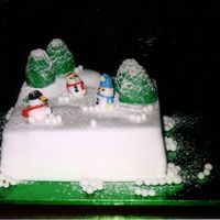 Christmas Snowmen Chocolate mud cake, covered in white fondant, fondant sculpted trees and snowmen.