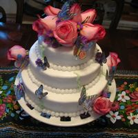 "Kim's Butterflies   6"", 8"", 10"" single layers stacked with white buttercream and edible wafer paper butterflies and fresh roses."