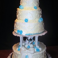 White Scrolls With Aqua Flowers   My first wedding cake. Buttercream icing, royal icing flowers, and fondant bow.