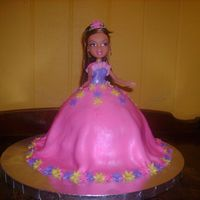 Bratz Doll Birthday Cake For My Grandaughter This is a doll cake. It is a white cake with buttercream icing, covered in fondant. The skirt part is brushed in super pearl luster dust to...