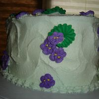 "Wilton Violet Cake Oval 4"" cake w/buttercream icing, violets and leaves are Royal icing"
