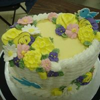 "Wilton Course Ii Class Graduation Class Oval cake 4"", basket weave in buttercream, with royal icing mixed spring flowers. Birds are color flow."
