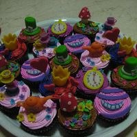 Alice In Wonderland Cuppies chocolate cupcakes topped with objects from alice in wonderland