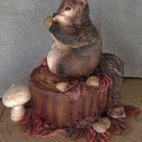 Squirrel Squirrel and stump are all cake, iced in buttercream and airbrushed. Leaves and acorns are piped on with buttercream. Mushroom is meringue...