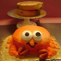 Crab Cake Two layer cake, beveled, iced in buttercream. Legs piped on with buttercream...pinchers, fortune cookies airbrushed orange. Sand, graham...