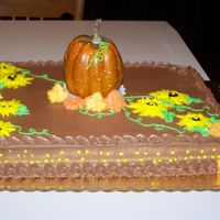 100_0406.jpg  Sheet cake with sunflowers and a pumpkin all bc except pumpkin which was plastic made leaves on it to be more realistic. The small...