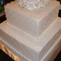 Roses, Pearls, And Diamonds Iced in buttercream, this small wedding cake was impressed with a diamond pattern, and accented with fondant pearls. The cake topper was...