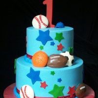 Sports Ball Cake First birthday cake iced in buttercream. Chocolate molded balls. Fondant and gumpaste decorations.