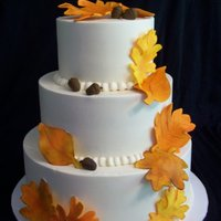 Autumn Wedding Cake...  Bride sent me a picture of a cake from Pink Cake Box. Leaves are fondant, dusted with petal dust. Acorns are fondant, cake iced in ivory...
