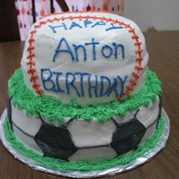 "Soccer And Baseball Cake Tiered cake. 10"" and 8"" layers. Buttercream frosting."