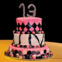Pink Black And Grey A three tiered cake for a 13th birthday. It is a buttercream base with fondant accents.