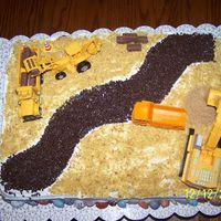 Construction Cake  This was done for a one year olds birthday. Everything is edilble except the toy tractors and trucks. This was a yellow butter cake with bc...