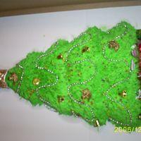 Oh Christmas Tree  Used the Wilton Tree Mold. Decorated with angel pics and various candles shaped as toys (football, hockey pucks, etc. Had bead strands,...