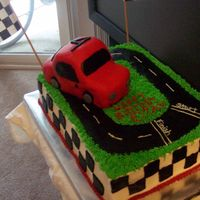 Race Car Track Birthday Cake This is a 2 layer, 11X15 vanilla chocolate chip and chocolate chocolate chip with raspberry mousse filling. Car is all fondant. I don'...