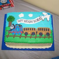 Thomas Train Cake  I made this cake for a friend's son's 2nd birthday. He is a huge Thomas the Tank Engine fan. The train cars, airplane, and tree...