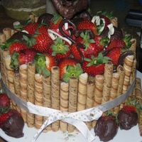 Larrys_Bday.jpg german chocolate cake and frosting with strawberries and pirouttes