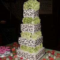 Kiley's Wedding Cake  4 tiered cake iced in bc, decorated with brown scrolls and green hydrangeas between each tier. Cake design is based off of a picture of a...