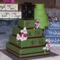 Oriental Themed Wedding Cake  This is another dummy cake. covered in fondant silk orchids and ribbon onthe borders of cake. words painted by hand from a very good friend...