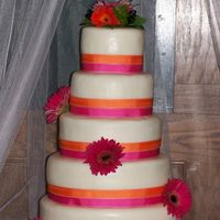 Orange And Pink Gerber Daisy Wedding Cake  5 Tiered round wedding cake. All tiers are different kinds of cake. covered in mmf and two layers of ribbon around the cake. Real flowers...