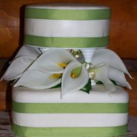 Cala Lily Wedding Cake  This cake is covered with fondant and a green ribbon around to match wedding colors. Lilies are fake and arrangment is made to take off and...