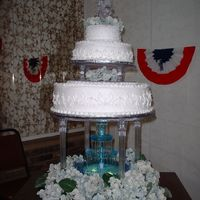 Dscf0015.jpg My first wedding cake. Luckily it was a freebie for a friend's son. I put the 2 smal tiers together at home and they shifted a little...