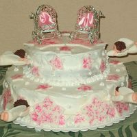 Angel Babies  This is the cake I made for my twin daughters' baby dedication. In the baby carriages, I put pieces of pink satin so it would look...