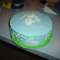 Happy Easter Easter cake for the family. Yellow cake, BC frosting, fondant bunnies, royal icing flowers and mini eggs on sides.