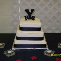 Simple Wedding Cake Vanilla cake with ivory buttercream frosting. Black ribbon around each tier. The bride made the initials for the cake.