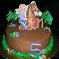 "Ambers 5Th Bday 8"" Choc cake with rasp filling. Iced in B/C. Choc mountains, trees and rocks. Edible image of ""Barbie on a horse"", backed..."