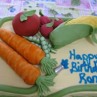 Ron's Birthday Cake  Garden theme birthday cake. Fondant covered rice krispie treat veggies. Buttercream hose creates top and bottom cake border, blue piping...