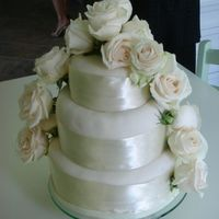 Ivory And Creme Wedding Cake Round 3 tiered wedding cake with ivory icing, creme ribbon and creme roses