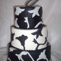 Black & White Cake  Chocolate cake with raspberry filling, covered in buttercream (top and bottom tier chocolate buttercream). Fondant accents and gumpaste...
