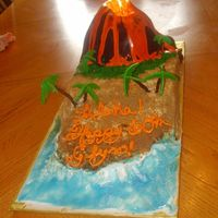Volcano  Surprise 60th birthday cake. The Volcano is covered in chocolate fondant, the sand is brown sugar, and the palm trees are made from...