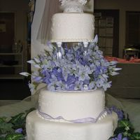 Lilac Anniversay 3 Tier Cake. Pillar & Stacked Construction. 2 Rounds and 1 Petal. Fondant over Buttercream w/white scrollwork.