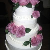 Wedding Cake With Purple Roses I had to bake and assemble this cake during 95 degree weather and 90% humidity! And then the wedding was outdoors...next to the ocean!...