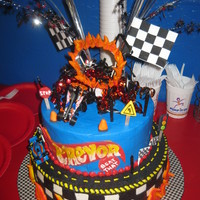 Racing Cake Race car on a wire jumping thru icing flames, buttercream icing all over w/ royal icing lettering fondant signs, banner and cones. Fire...