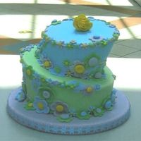 "Floral Delight 6"" and 8"" topsy turvy tiered cake in shades of blue, violet, green and yellow decorated with fondant fantasy flowers"