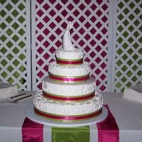 4 Tier Cake With Pink & Green Ribbon This is the biggest cake I have ever done. I was very nervous to stack it. All buttercream with scroll work. Pink and Green satin ribbon.