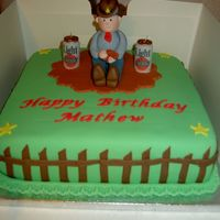 "Cowboy Birthday Cake 10"" square chocolate cake covered with green sugarpaste and sugarpaste model cowboy. Candles are beer cans."