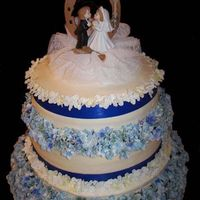 "First Wedding Cake This is my first solo wedding cake. It's made out of 18"" 16"" and 12"" rounds. At brides request all the flowers are silk..."